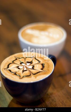 Le tazze con latte art da Barista s sogghignato quotidiano proprietario Ryan Dennhardt campione del mondo di Ultimate Foto Stock