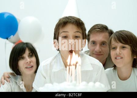 Ragazzo circa a soffiare le candeline sulla torta di compleanno, famiglia guardare Foto Stock