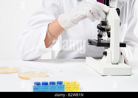 Scienziato con microscopio Foto Stock