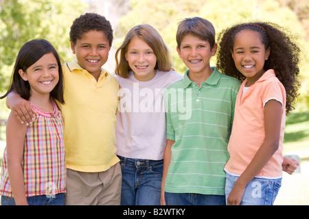 Cinque giovani amici in piedi all'aperto sorridente Foto Stock