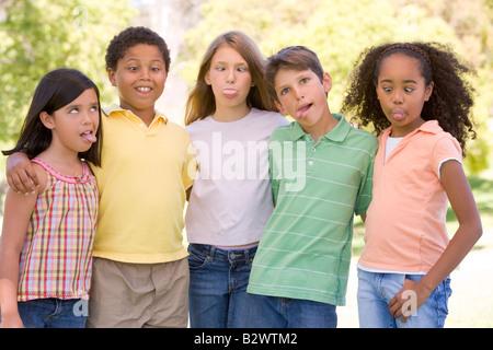 Cinque giovani amici in piedi all'aperto facendo facce buffe Foto Stock