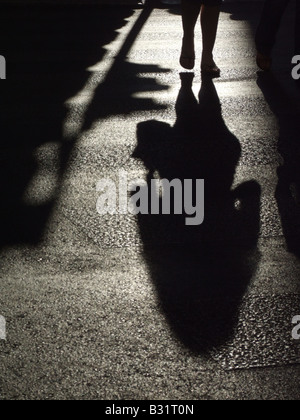 Persona della ombra scura sulla superficie stradale in città Foto Stock