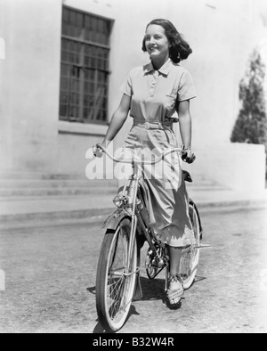 Giovane donna in sella la sua bici Foto Stock