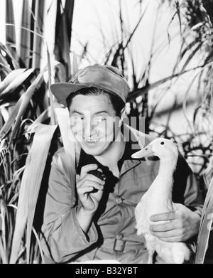 Giovane uomo sorridente tenendo un anatra Foto Stock