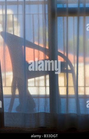 Vista di una sedia sul balcone mediante tendine. Foto Stock