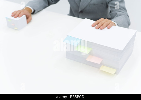Pile di carta con note adesive che li dividono, uomo mettendo una mano su ciascuna pila Foto Stock