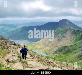 Due persone che camminano giù il Pyg via verso Llyn Glaslyn e Llyn Llydaw sui ripidi pendii superiore di Mount Snowdon Foto Stock