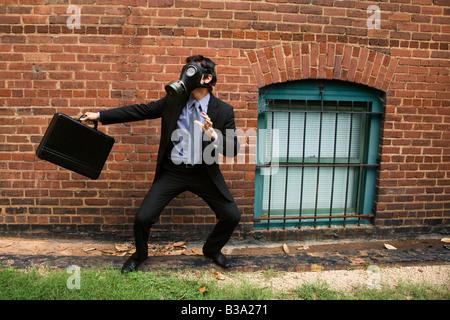 Imprenditore in piedi accanto al muro di mattoni che indossa maschera a gas in posizione di combattimento