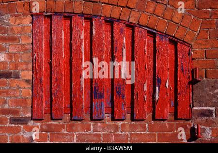 Peeling vernice rossa sulla finestra otturatore del mattone antico fienile, Staffordshire, Inghilterra Foto Stock