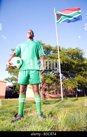 Monkeyapple aFRIKA raccolta grande magazzino ! Giocatore di calcio posa con palla sotto South African bandiera Foto Stock