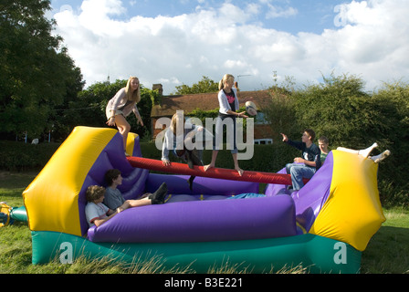 Gli adolescenti giocando su un gonfiabile castello gonfiabile party all'aperto Foto Stock