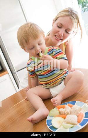 La madre e il bambino in cucina mangiare la frutta e la verdura Foto Stock