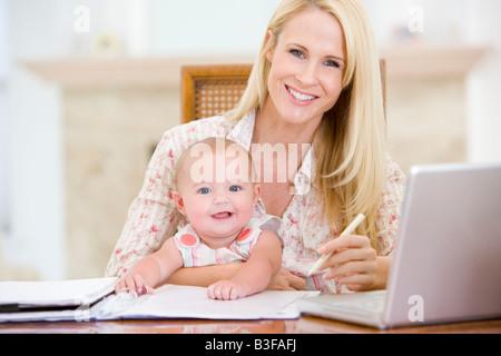 La madre e il bambino nella sala da pranzo con laptop sorridente Foto Stock