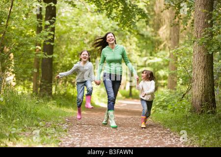 La madre e le figlie saltando sul percorso sorridente Foto Stock