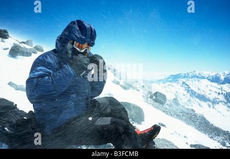 L'alpinista esposta al vento forte e neve sulle rocce Pastuckhov a 4690m sul normale percorso verso la vetta del Foto Stock