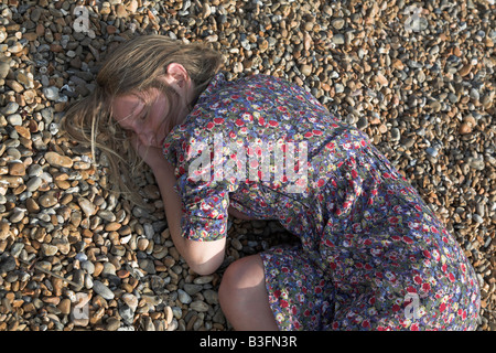 Giovane donna rannicchiato sulla spiaggia di ciottoli da soli Foto Stock