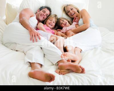 Famiglia giacente in letto sorridente Foto Stock