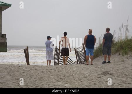 Quattro giovani uomini guardano il surf in spiaggia di Jacksonville in Florida durante la tempesta tropicale Hanna Foto Stock
