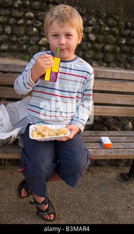 Cinque anni di vecchio ragazzo di mangiare patatine al di fuori seduta sul banco e avente un drink