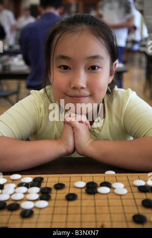 Canadese cinese ragazza che gioca andare oriental strategic board game Foto Stock