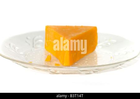 Un cuneo di formaggio cheddar su una piastra trasparente. Foto Stock