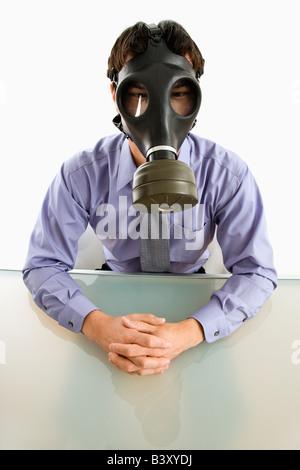 Imprenditore seduto in camera bianca indossando maschera a gas