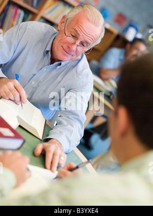Due uomini in biblioteca con taccuini parlando (messa a fuoco selettiva)