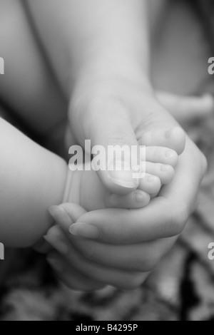 Close-up di una madre che tiene il suo bambino il piede in mano l'immagine monocromatica. Foto Stock