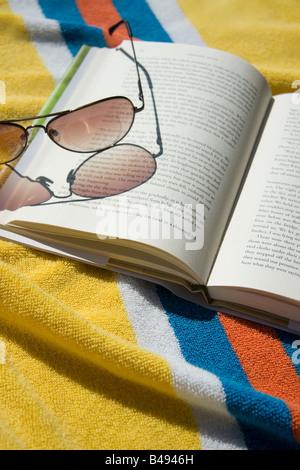 Aprire il libro e gli occhiali da sole sul telo da spiaggia Foto Stock