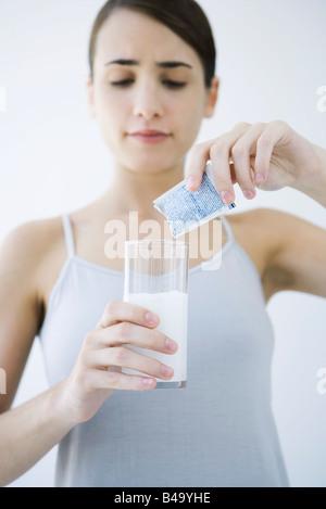 Donna versando medicina effervescente in un bicchiere di acqua Foto Stock