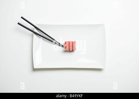 Maki sushi arrotolato in rosso flying fish roe accanto a bacchette sulla piastra di sushi, vista aerea Foto Stock