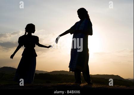Due sorelle indiane danza su una roccia al tramonto silhouette. Andhra Pradesh, India Foto Stock