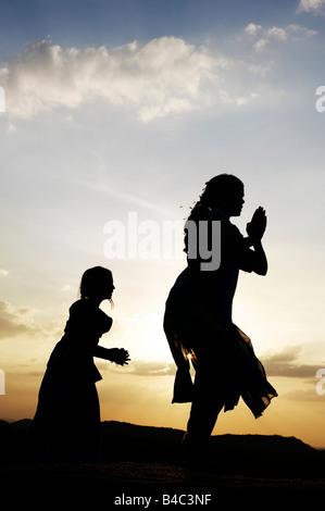 Due sorelle indiane eseguendo un indù danza devozionale su una roccia al tramonto silhouette. Andhra Pradesh, India Foto Stock