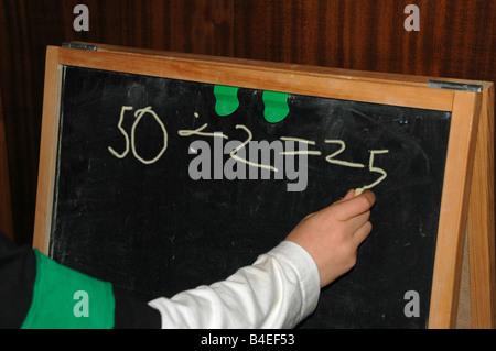 Un giovane ragazzo scrive un'equazione su una lavagna. Foto Stock