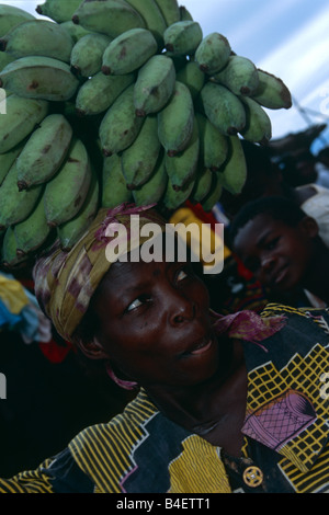Fornitore di banane con banane verdi mazzetto sulla testa. Uganda.