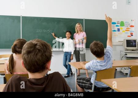 Un insegnante e uno studente alla lavagna, rivolta verso la classe Foto Stock