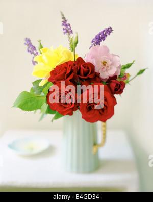 Rosa gialla e rose rosse in caraffa blu su un tavolo bianco Foto Stock