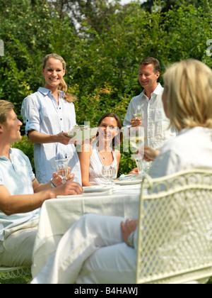 Cinque persone celebrare in un party in giardino Foto Stock