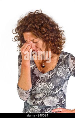 Pizzicare il ponte del naso con gli occhi chiusi indica un umore di valutazione negativa in questa donna Foto Stock
