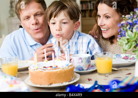 Ragazzo soffiare il suo compleanno candele Foto Stock