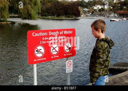 Un giovane ragazzo lettura un avviso di sicurezza firmare da un lago in helston,cornwall, Regno Unito Foto Stock