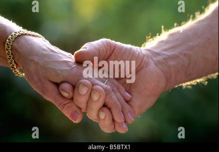 Tenere la mani - due anziani sposati in amore tenendo le mani all'aperto Foto Stock