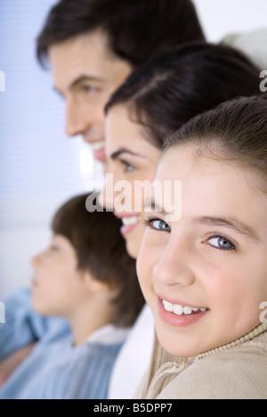 Ragazza seduta con la famiglia, sorridente sulla spalla in telecamera, close-up Foto Stock
