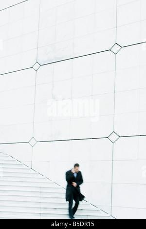 Imprenditore scendendo le scale per esterni, parlando al cellulare, tenendo rivestire chiuso contro il vento Foto Stock
