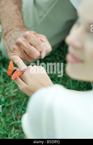 Butterfly sbarco sulla ragazza adolescente la mano, uomo di toccare la mano con il dito, al di sopra della spalla Foto Stock