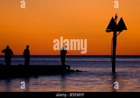 Sagome di tre uomini la pesca al tramonto in Avon, NC. Foto Stock