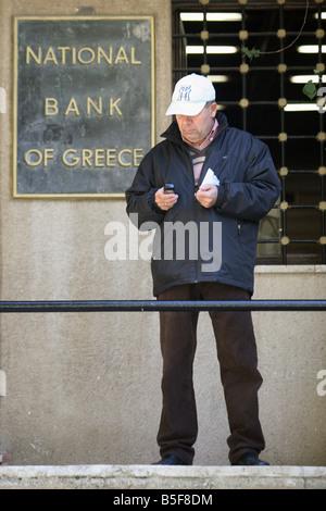 Uomo di fronte a un ramo della Banca nazionale di Grecia a Rodi, Grecia Foto Stock