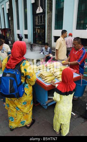Una donna e bambino indossa red head sciarpe ordinare alcuni hot sulla pannocchia di mais da un venditore ambulante Foto Stock