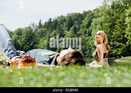 Giovane donna guardando il cielo mentre il suo fidanzato dorme in erba Foto Stock