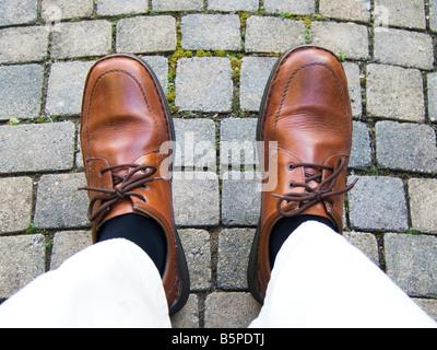Un uomo in piedi in scarpe marrone Foto Stock